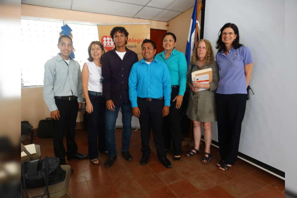 Byron Arias, de camisa celeste, junto a compañeros de clases y autoridades de la UCA durante la presentación de un proyecto con el que se graduó como ingeniero en sistemas. Cortesía | Niú